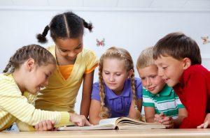 Children gathered around book